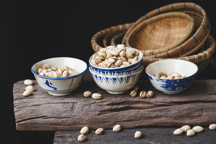 Pistachio nuts ASIA Dark Food And Drink Nature Plant Seed Vietnam Bamboo Basket Bowl Close-up Food Nutrition Old Wood Pistachio Pistachio Nuts Pottery Roasted Sweet Vitamin