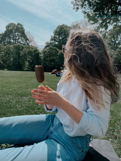 Side view of woman holding popsicle while sitting in park