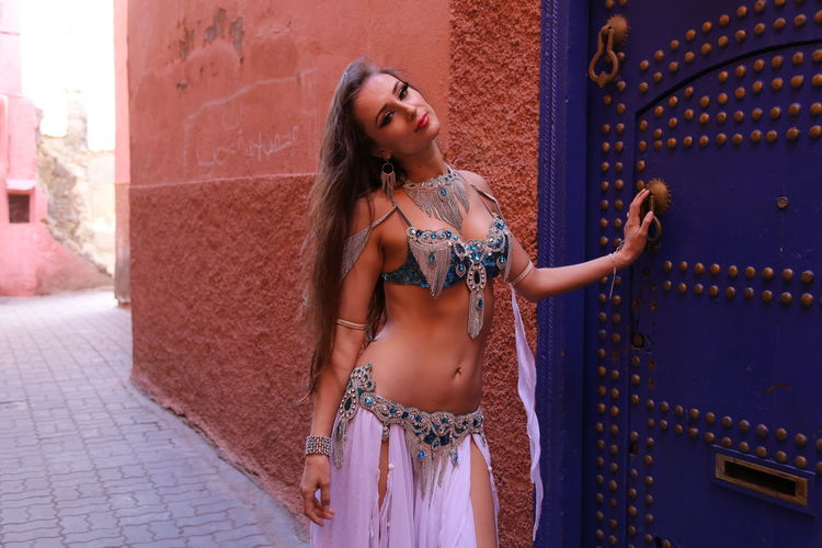 Portrait of beautiful young bellydancer wearing her belly dancing outfit and standing to a blue door