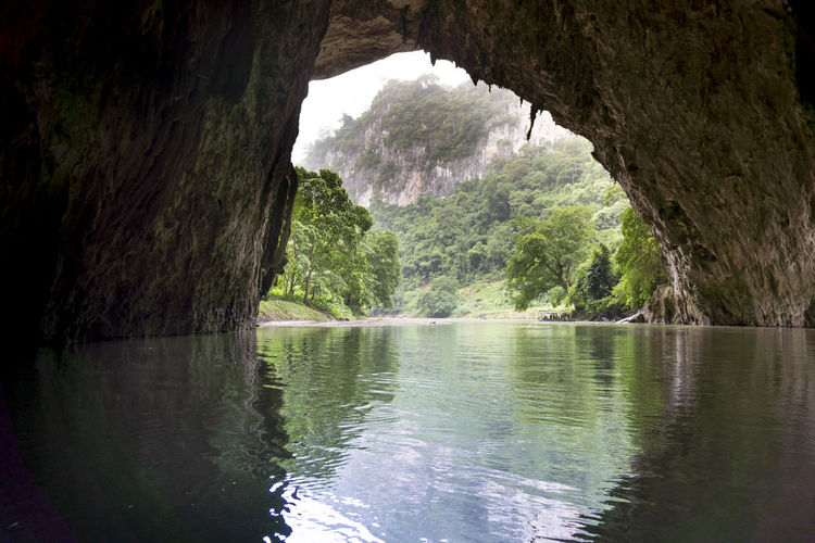 Beautiful natural scenery of Phong cave with boat tour at Ba Be Lake Nation Park is a famous travel destination in Bac Kan province, Vietnam. Ba Bé Lake Bac Kan Tourist Transportation Travel Beauty In Nature Boats Cave Destination Discovery Environment Fishing Foggy Forest Jungle Mountain Nature Outdoors Rock Scenery Scenics - Nature Tourism Tranquility Tropical Vacation