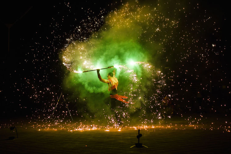 Man with fire crackers at night