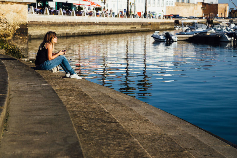 Woman sitting near the harbor of Faro, Portugal Algarve Harbor Harbour Stairs Travel Adult Architecture Boat Canal Casual Clothing Contemplation Leisure Activity Lifestyles Mode Of Transportation Nautical Vessel One Person Outdoors Real People Relaxation Sitting Transportation Travel Destinations Water Women