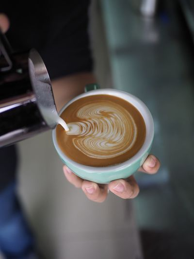 Cropped Hand Of Person Pouring Milk In Cappuccino