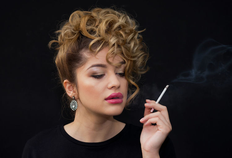 Portrait of a beautiful young girl smoking a cigarette, on a black background Small Pleasures Thinking Addiction Adult Attractive Bad Habit Beautiful Woman Black Background Cigar Cigarette  Curly Hair Enjoying Headshot Lifestyles One Person People Portrait Real People Sensual Girl Smoke - Physical Structure Smoking - Activity Smoking Issues Studio Shot Young Adult Young Women