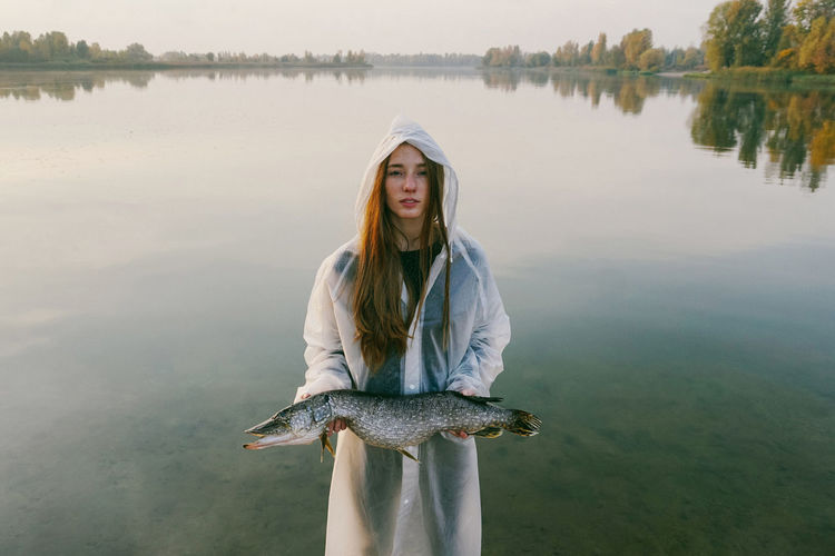 Water Lake Leisure Activity Nature Lifestyles Reflection Beauty In Nature Outdoors Fish Fishing Girl Lake View Reflection Raincoat Beauty In Nature Beautiful Portrait Hairstyle Real People Young Adult Casual Clothing Front View Calm Tranquility Tranquil Scene