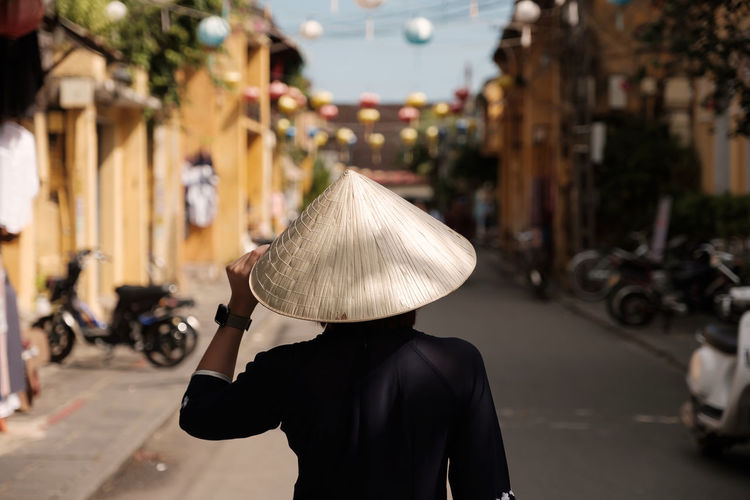 girl wearing vietnam hat or non la and sightseeing at heritage village in hoi an city in vietnam