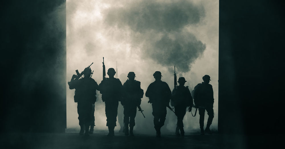 Silhouette army with guns walking during war
