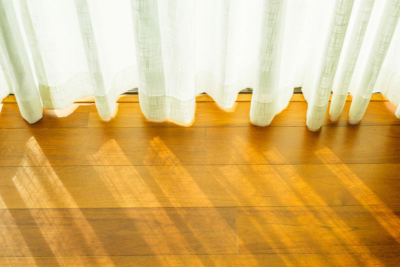 High angle view of white curtain hanging over hardwood floor