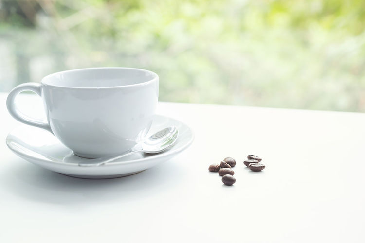 Close-Up Of Coffee Cup With Beans On Table Against Window