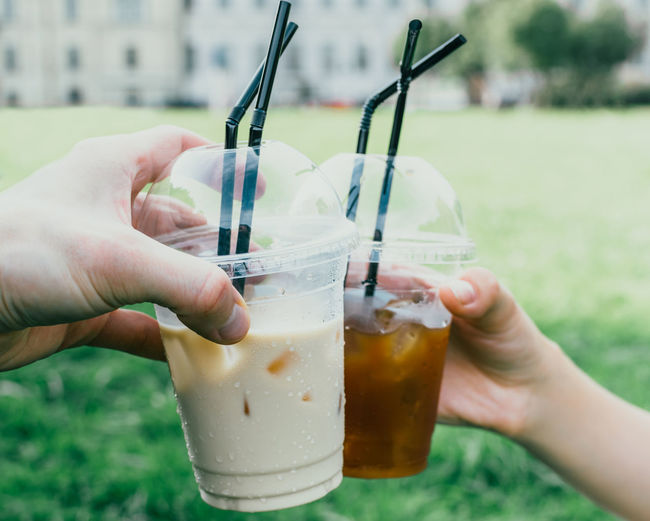 Close-up Coffee Coffee Time Day Drinks Eating Food Freshness Holding Human Finger Ice Coffee Leisure Activity Lifestyles Outdoors Park Part Of Personal Perspective Street Food Summer Unrecognizable Person