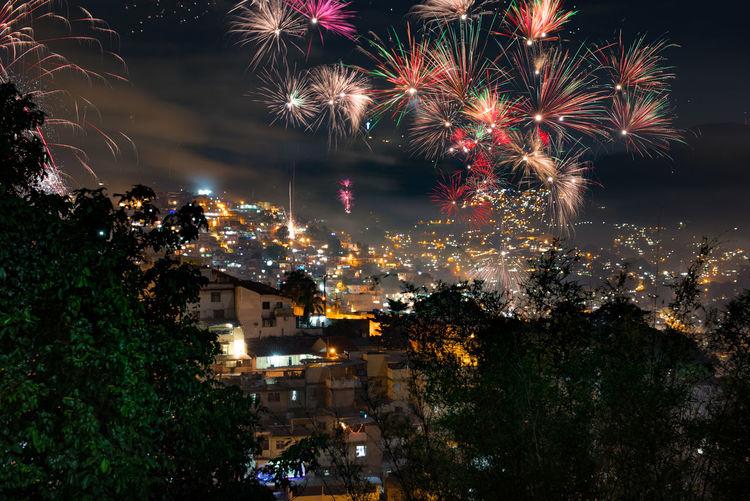 Firework display over illuminated cityscape at night