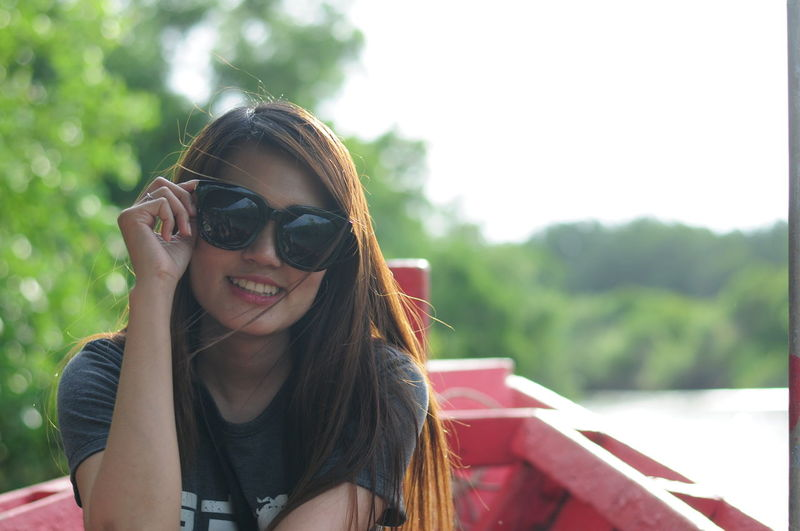 Portrait Of Woman Wearing Sunglasses While Sitting On Boat In Lake