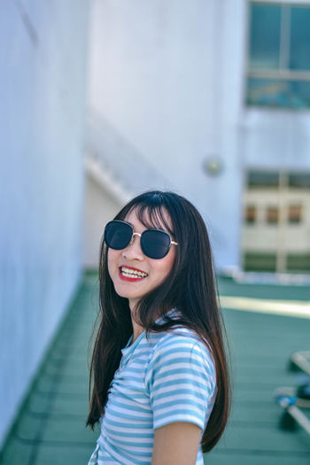 Cheerful young woman wearing sunglasses standing against building