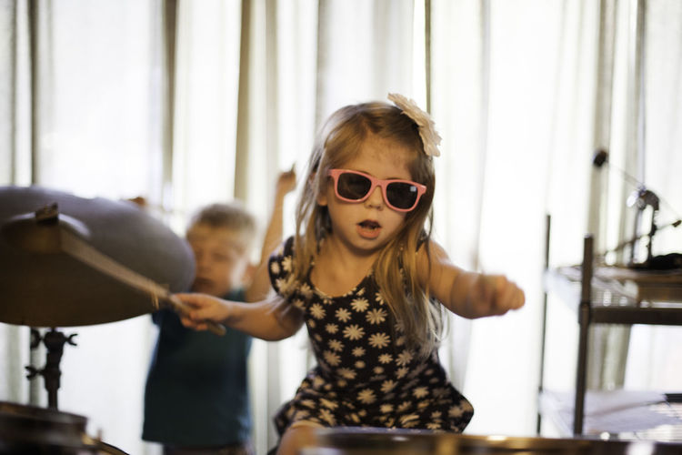 A brother and sister play the drums at their home. Child Musician Childhood Cool Cymbal Domestic Life Drumming Drums Drumset Indoors  Loud Musician Playing Drums Sunglasses Togetherness Two People Enjoy The New Normal