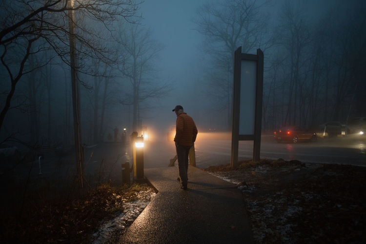 Rear view of man standing on street at night during winter