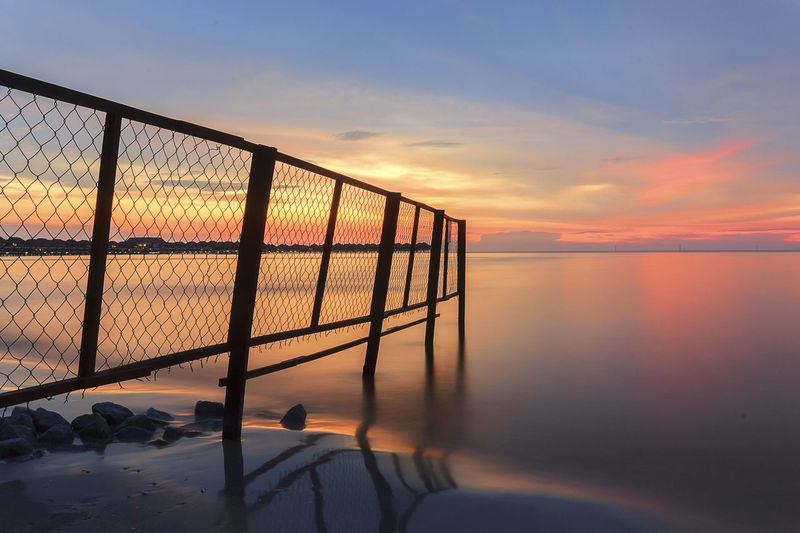 Fence way to the sea beach and beautiful sunset Bagan Lalang Beauty In Nature Cloud Cloud - Sky Concept Fence Leisure Activity Lifestyles Malaysia Nature Orange Color Outdoors Scenics Sky Sun Sunset Tranquil Scene Tranquility Travel Destinations Unrecognizable Person
