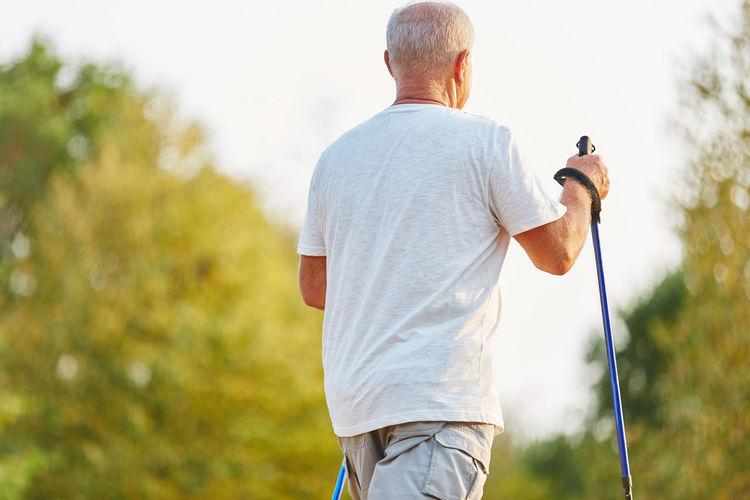 Rear View Of Senior Man Walking Against Trees