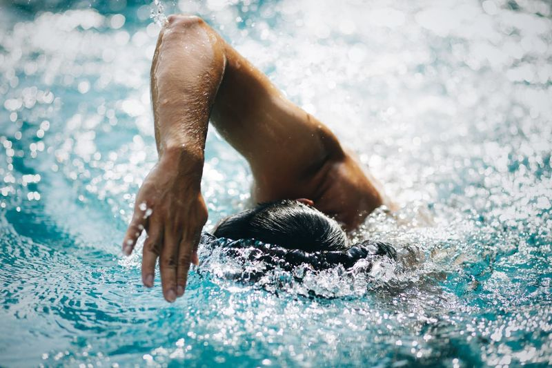 Midsection of man swimming in pool