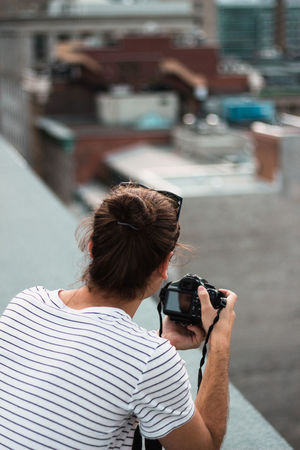 The Roof Cityscape Leather Man Bun Montréal Roof Rooftop Scenery Striped Shirts Camera - Photographic Equipment Digital Camera Digital Single-lens Reflex Camera Leisure Activity Lined Shirt Mobile Phone Outdoors Photographer Photographing Photography Themes Rear View Rooftops Technology Watch Watches Wireless Technology