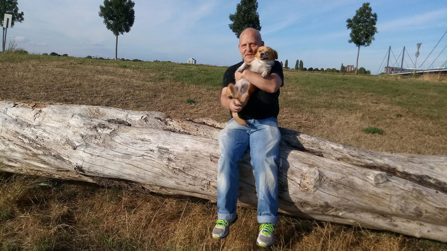 Full Length Of Man Carrying Dog While Sitting On Log Against Sky