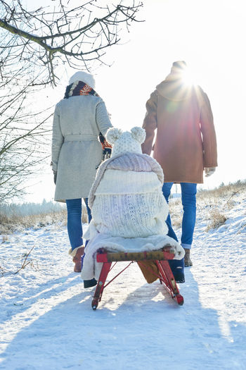 Rear view of people walking on snow field