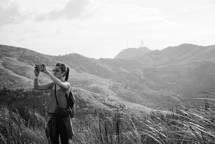 Young woman photographing from mobile phone while standing on mountain