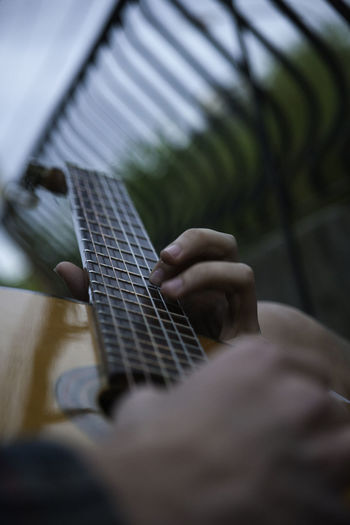 Cropped image of hands playing guitar