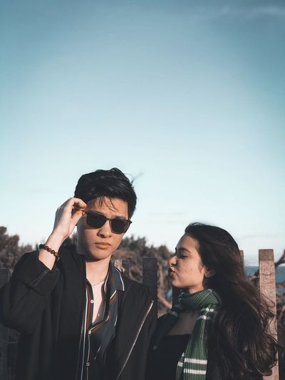 Young couple standing against sky