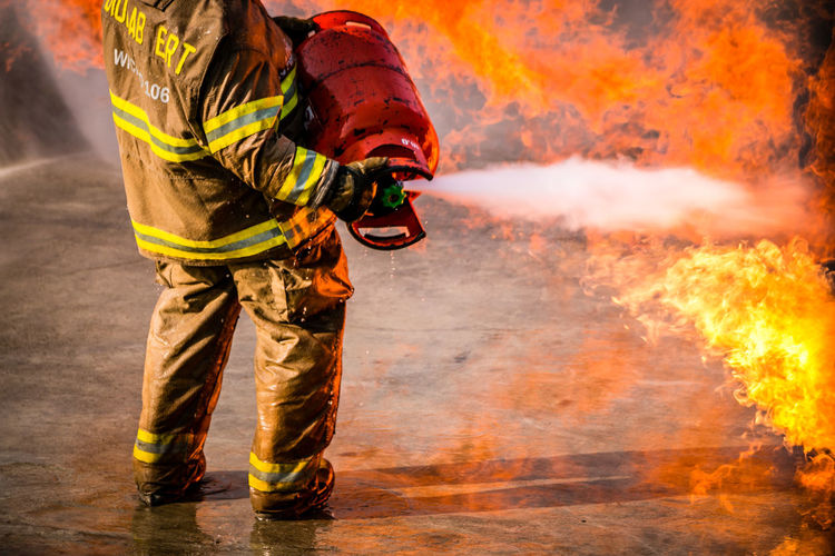 Accidents And Disasters Burning Clothing Fire Fire - Natural Phenomenon Fire Hose Firefighter Flame Headwear Heat - Temperature Helmet Heroes Hose Occupation One Person Outdoors Protection Protective Workwear Rescue Worker RISK Spraying Standing Uniform Warning Sign