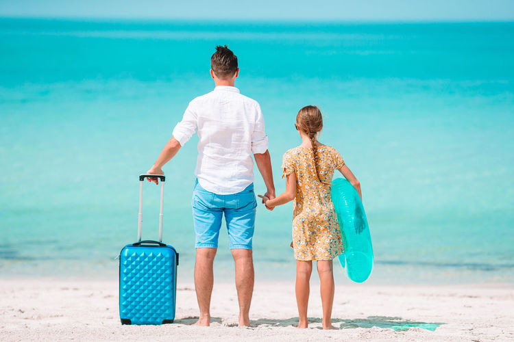 Rear view of father and daughter standing on beach