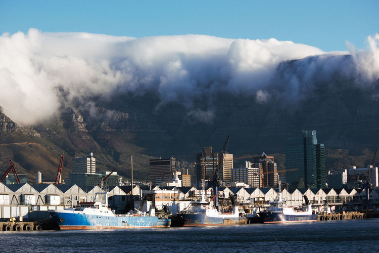 Fishing Vessels Moored In Cape Town Harbor Sky Table Mountain Table Mountain Cloud Clouds City Cityscape Cloudscape Buildings Harbor Port Pier Docks Water Warehouse Warehousing Boat Boats Ships Vessel Vessels Travel Destination Destinations Capital Cities  Vacation Industry Fishing Soft Beautiful View Urban Coastal Blue Red White Gray Green Brown Landscape Photograph Photography Colors Color Background Backgrounds Horizontal Cities Waterfront Architecture Nautical Vessel Transportation Building Exterior Built Structure Mode Of Transportation Sea Nature No People Day Cloud - Sky Commercial Dock Building Outdoors Mountain Range