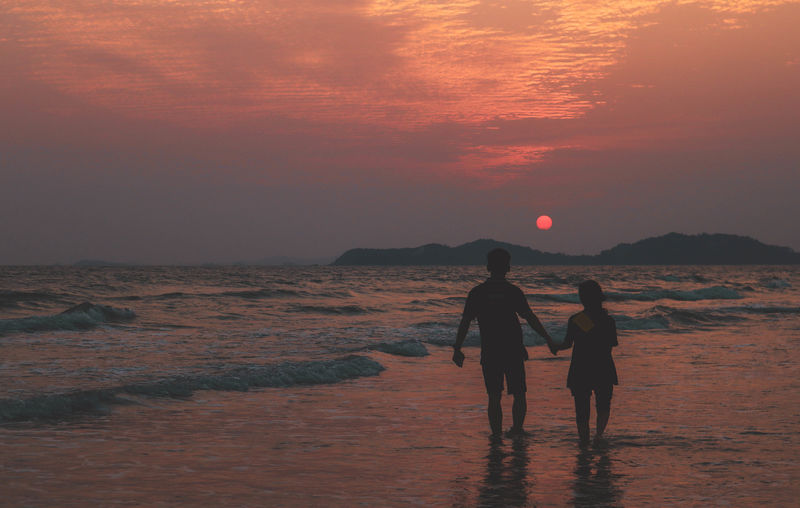 Rear view of silhouette couple standing in sea against sky during sunset