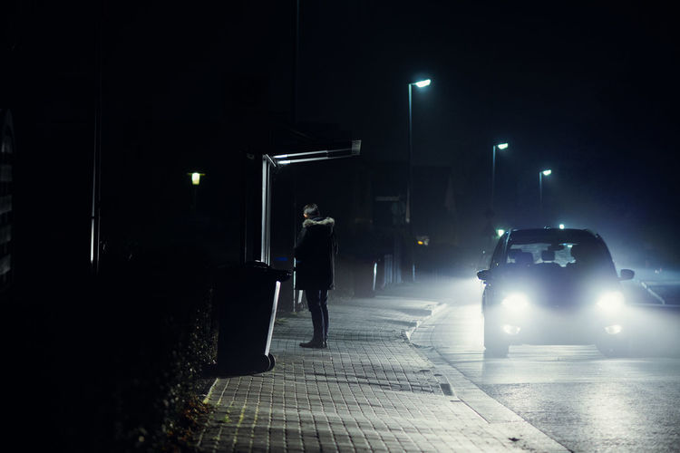 Rear View Of Man Standing Sidewalk At Night