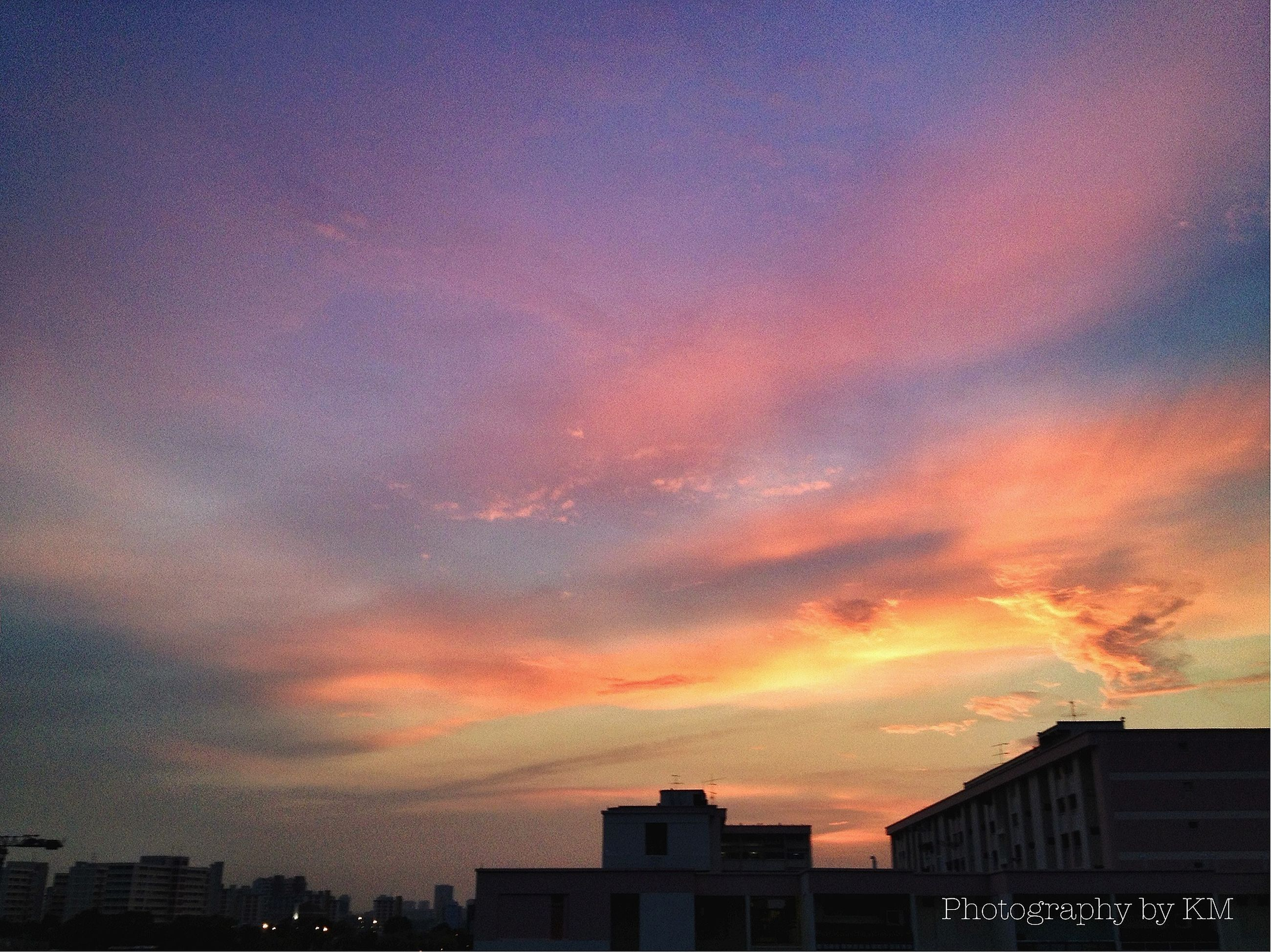 architecture, building exterior, built structure, sunset, sky, cloud - sky, low angle view, city, orange color, cloudy, silhouette, residential building, building, cloud, residential structure, dramatic sky, dusk, outdoors, weather, nature