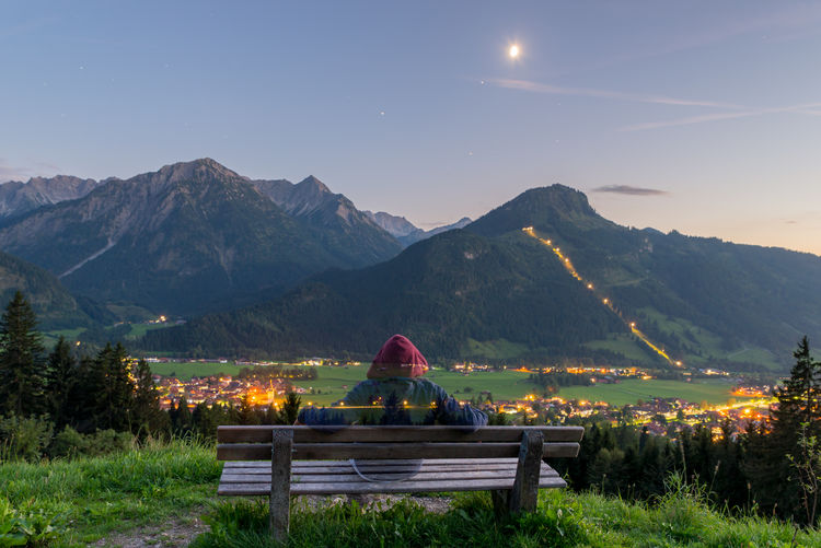 Woman sitting on bench against mountain