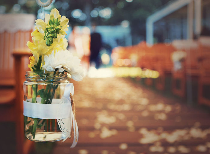 Close-up of flowers in jar hanging at restaurant
