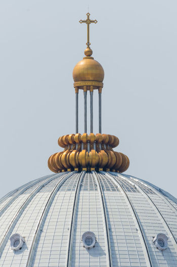 Low angle view of golden cross on building against clear sky