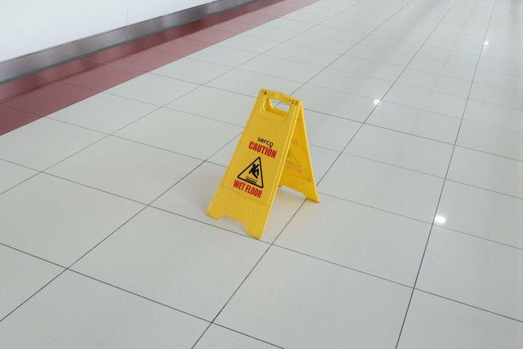 High angle view of arrow sign on tiled floor