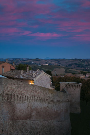 Romantic view of Corinaldo medieval village at sunset Castle City Sunset_collection Travel Architecture Building Exterior Built Structure City Cloud - Sky Corinaldo Dusk Fort Fortress Fortress Wall High Angle View Idyllic Medieval Medieval Architecture Old Residential District Sky Sunset Town Travel Destinations Wall