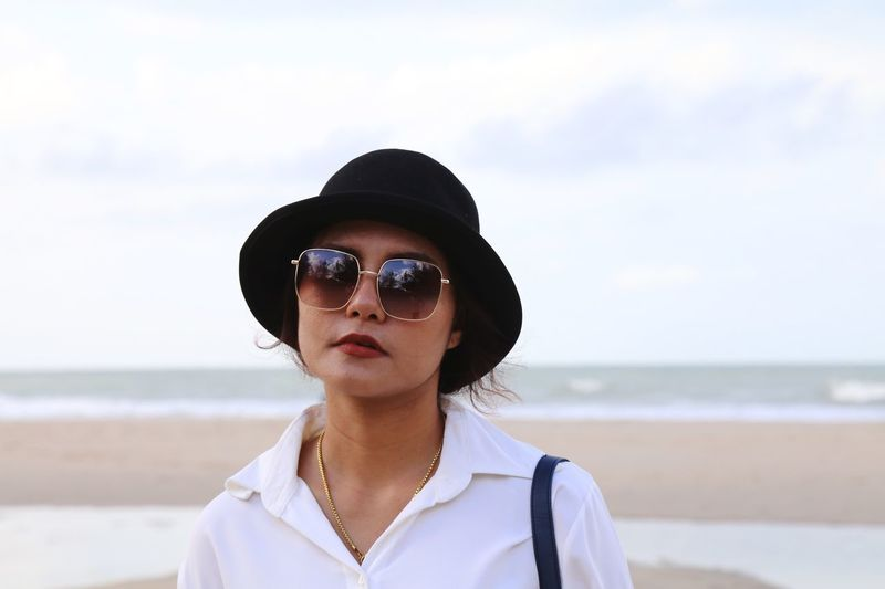 Portrait of woman wearing sunglasses while standing at beach against sky