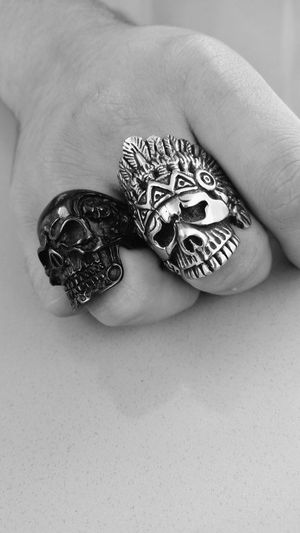 Cropped Image Of Man With Skull Rings On Table