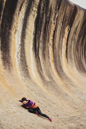 Young woman sliding on rock formation
