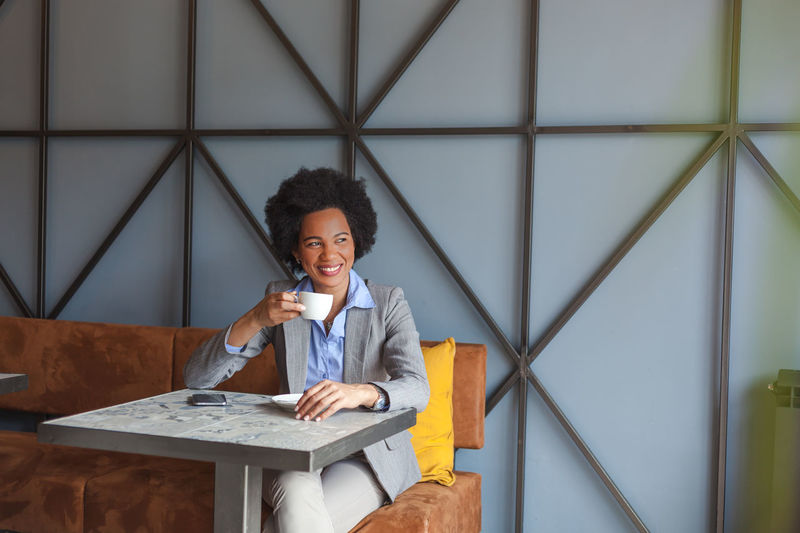Front View One Person Real People Smiling Happiness Table Holding Sitting Indoors  Young Adult Leisure Activity Portrait Curly Hair Emotion Lifestyles Women Cafe Coffee Coffee - Drink Coffee Cup African African American Suit Horizontal Serbia Break Business Business Finance And Industry Business Person Businesswoman Morning
