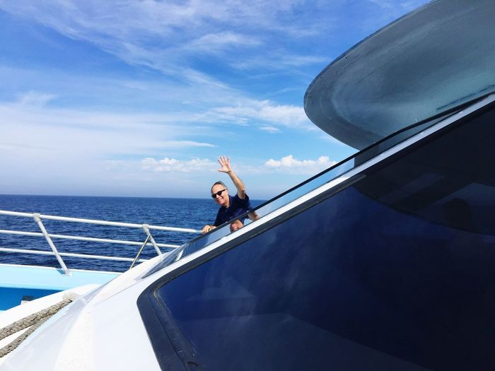 Man waving while traveling on yacht at sea against sky