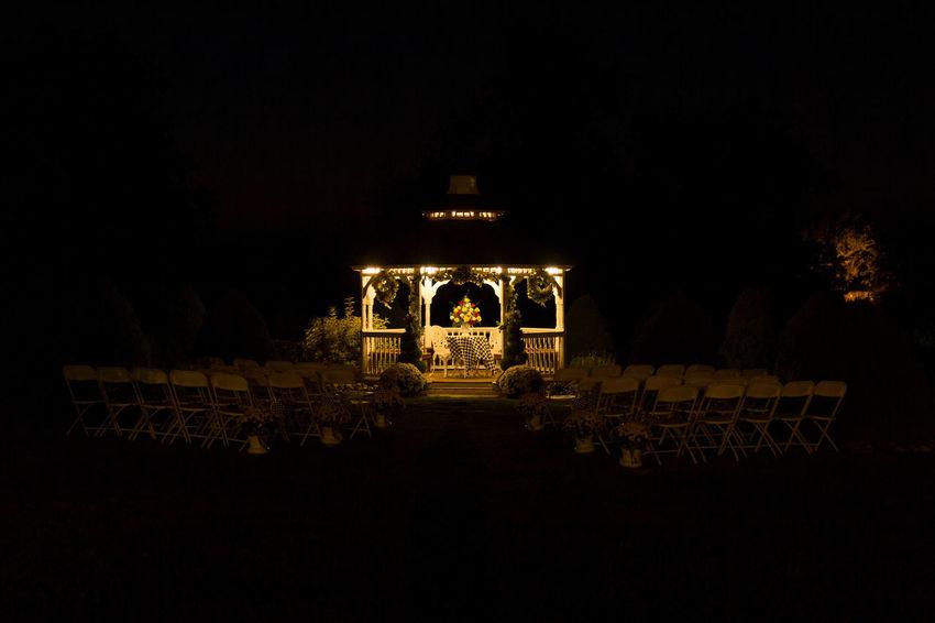 Wedding gazebo glowing in the darkness of night. Gazebo Jwhetzelphotography Gold Colored Chairs Wedding Wedding Photography Decorations Glowing Illuminated Tree Sky Lantern Carousel Bauble Entertainment Golden