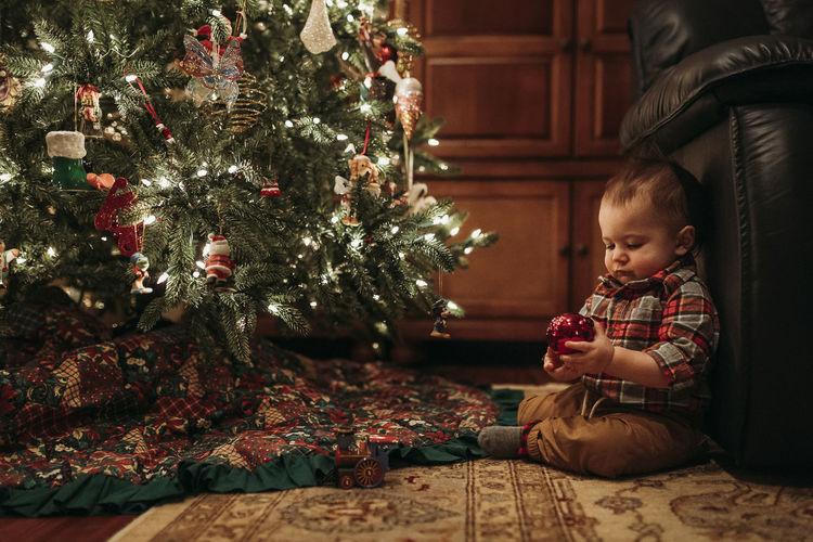 Boy sitting in christmas tree