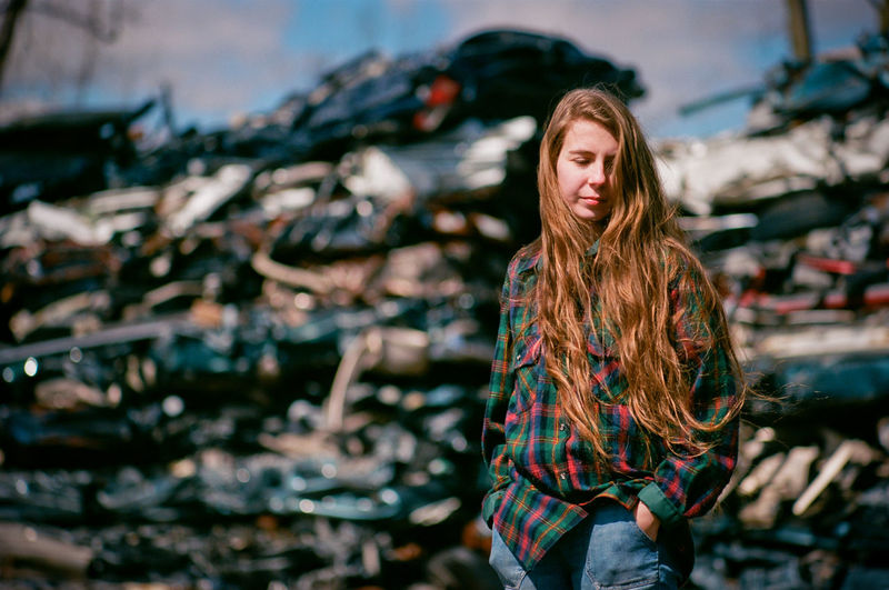 Young woman standing in an auto salvage yard