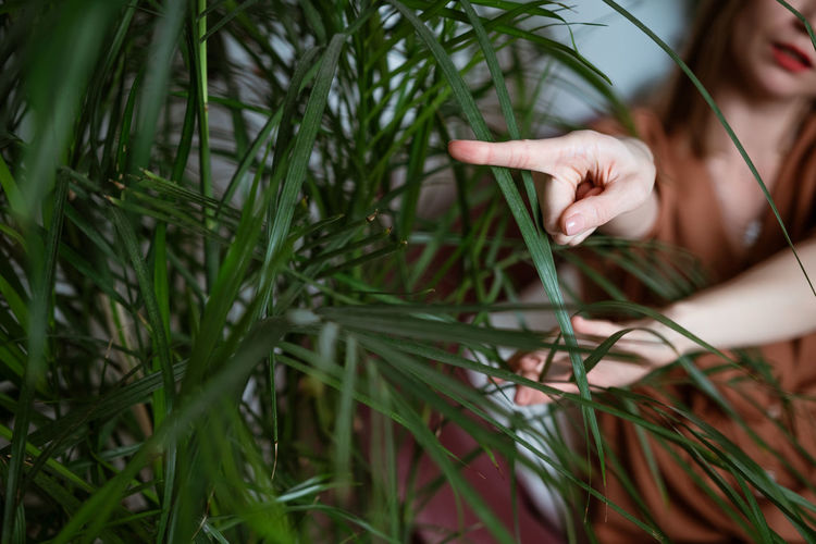 Woman shows her finger to the side against a background of green leaves