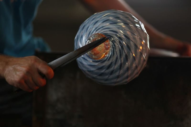 Cropped image of worker shaping glass in workshop