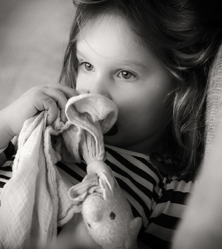 Close-Up Of Thoughtful Girl Sitting On Sofa